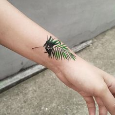 small leaf on wrist tattoo